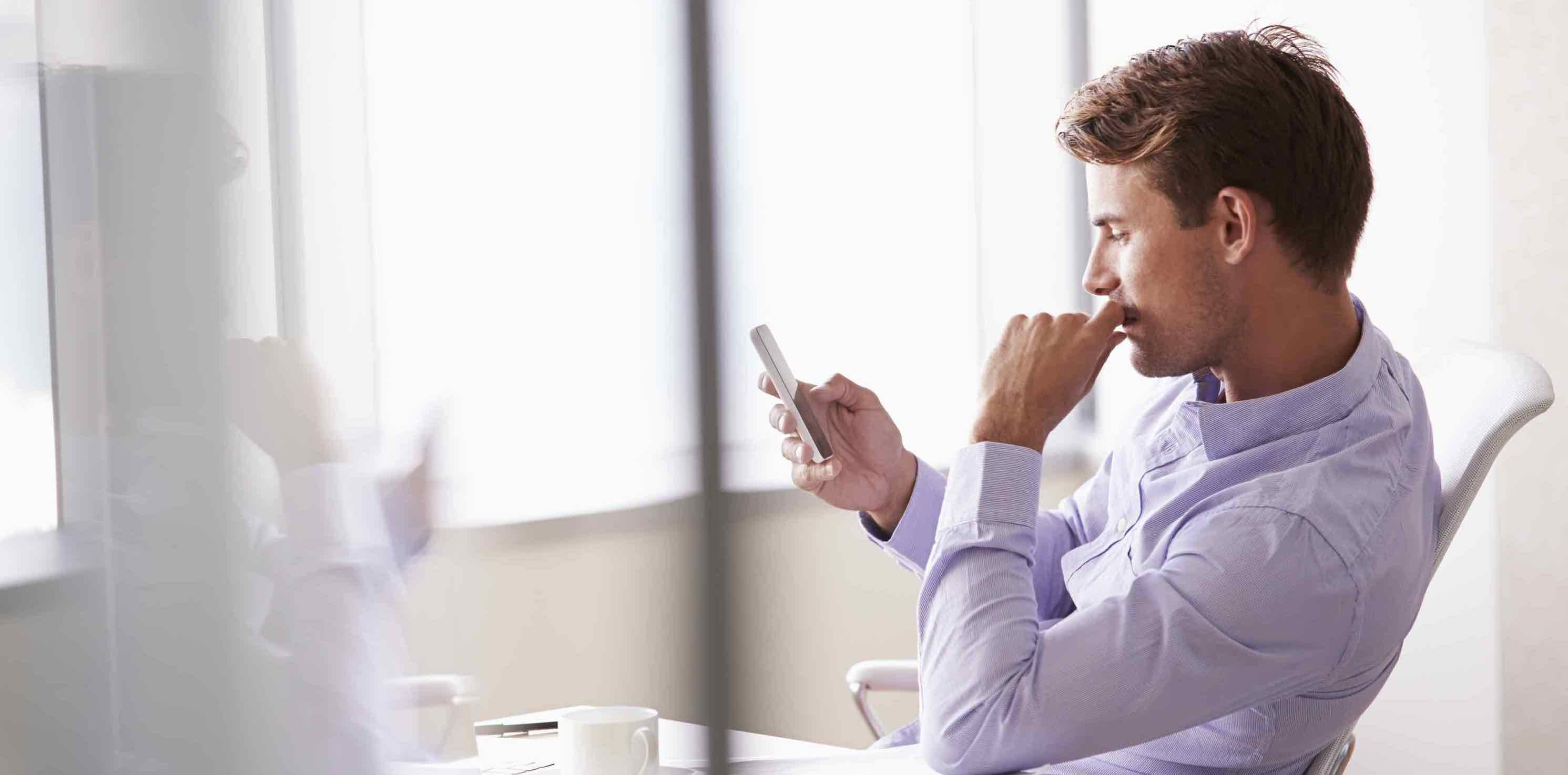 Casually Dressed Businessman Using Online Claims Management Software on His Mobile Phone In Office