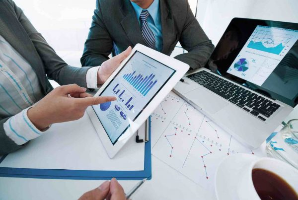 Group of executives discussing business activity graphs on tablet screen
